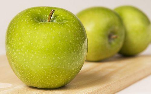 Зелёные яблоки на деревянной доске