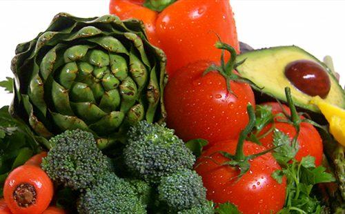 В груде овощей виднеются артишок, брокколи, перец, помидоры и авокадо