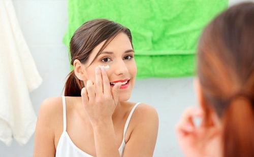 Молодая женщина накладывает перед зеркалом крем
