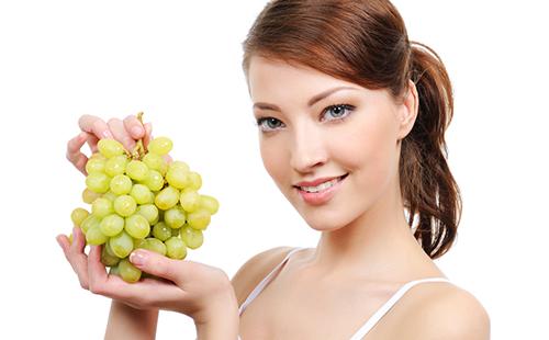 Женщина с кистью зелёного винограда