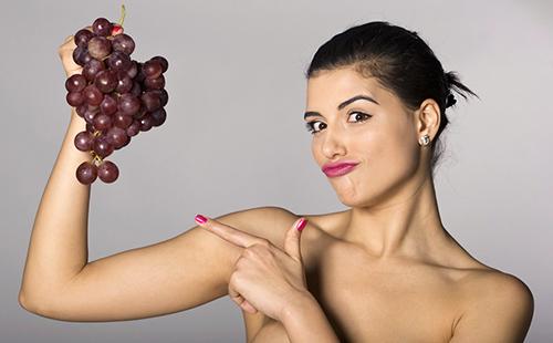 Женщина показывает пальцем на гроздь красного винограда