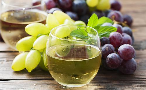 Светлый сок в стакане на фоне ягод
