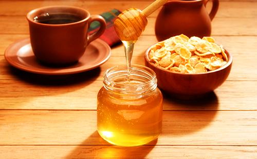 Баночка мёда и чашка кофе в тёплых тонах