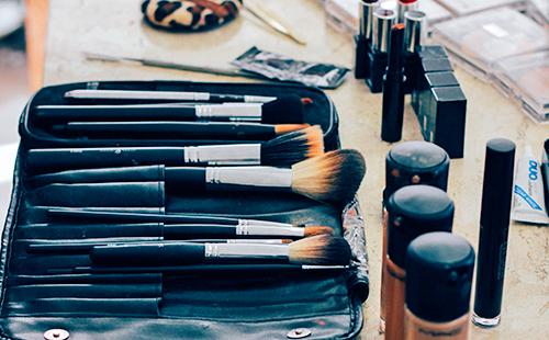 Кисти и баночки для макияжа лежат на столе