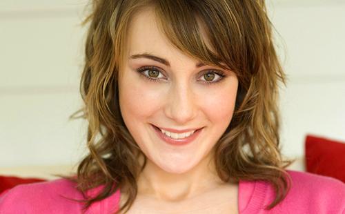 Славная улыбка девушки в розовой кофте