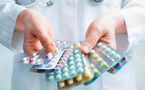 Руки держат пачки разноцветных таблеток