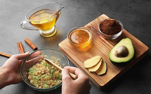 Женские руки смешивают масла, мёд и авокадо