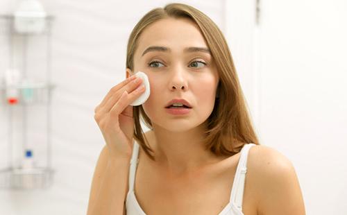 Красивая девушка очищает лицо ватным диском