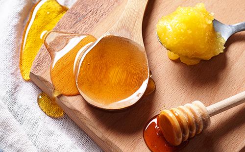 Разные сорта мёда разлиты на разделочной доске