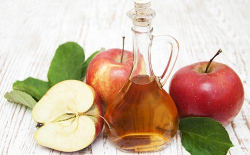 Кувшин с яблочным уксусом среди плодов